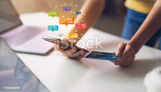 1016971522 istock photo Woman holding smartphone with icon discount label and cart online, credit card on the table. Concepts online shopping for convenience. 1153536291