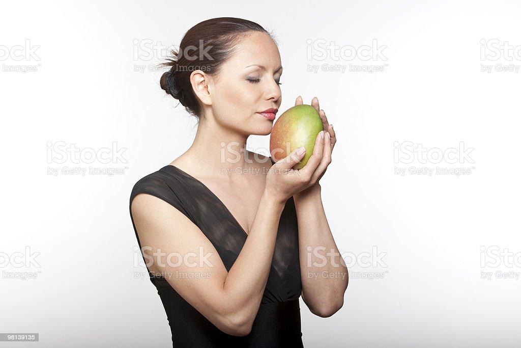 woman holding smelling mango royalty-free stock photo