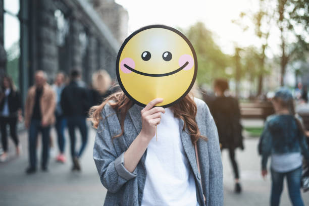 woman holding smiling sign on her face outside - excited emoji stock photos and pictures