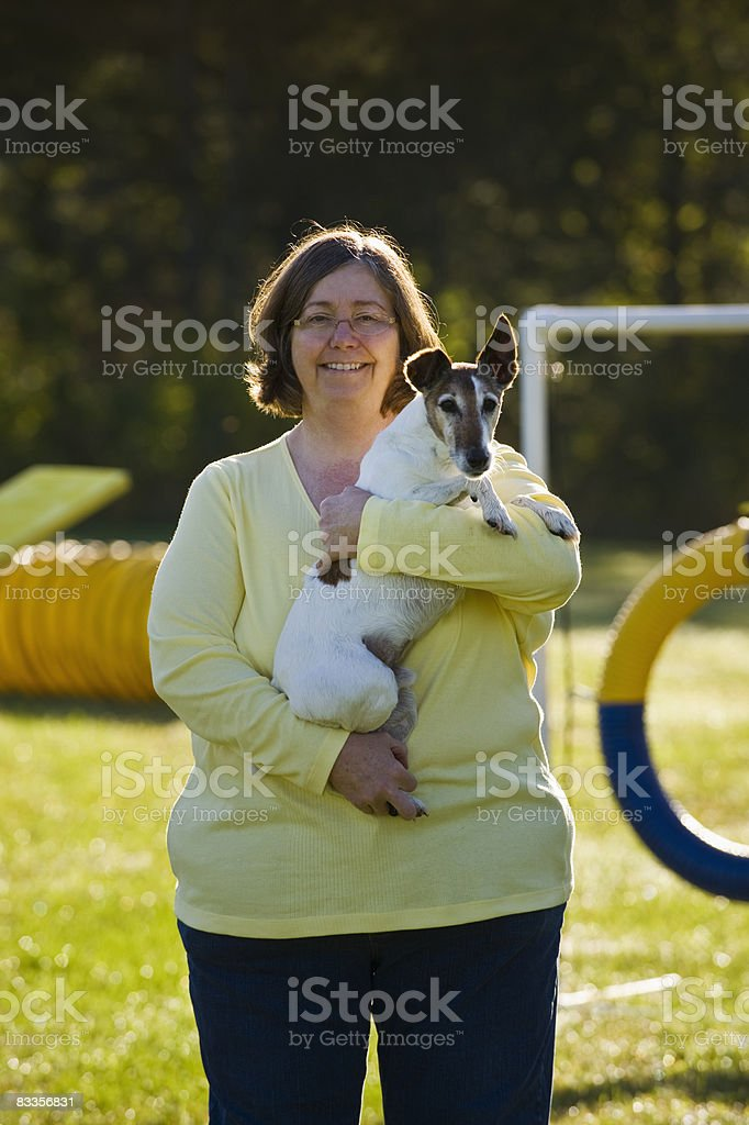 Woman holding Smooth Fox Terrier outdoors royalty free stockfoto