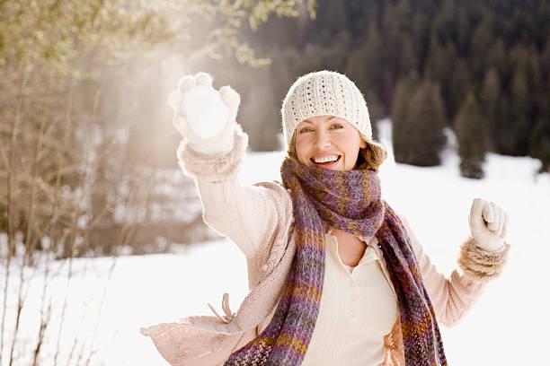 frau holding schneeball - mützenschal stock-fotos und bilder