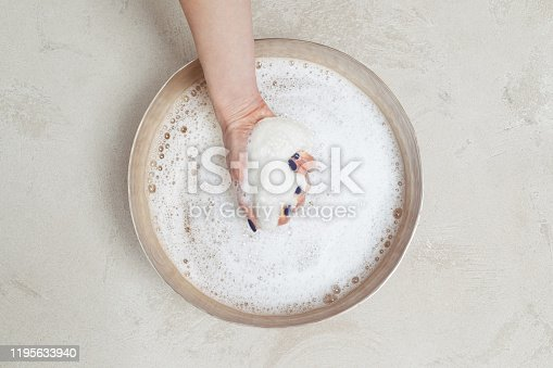 Hand of unrecognisable woman holding spa sponge in bawl with water.