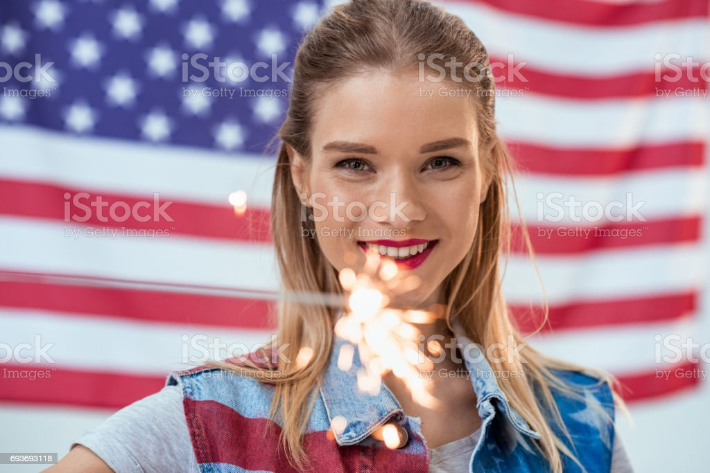 woman holding sparkler with American flag behind stock photo