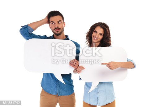 854381780istockphoto woman holding speech bubble points to thoughtful man 854381742