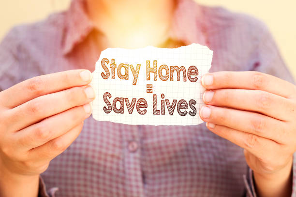 woman holding stay home means save lives tear paper woman holding stay home means save lives tear paper stay at home order stock pictures, royalty-free photos & images