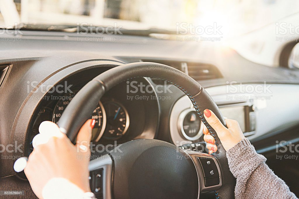 Woman holding steering wheel and driving car during day stock photo