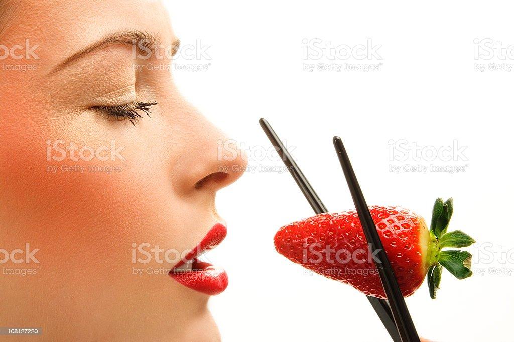 Woman Holding Strawberry Between Chopsticks royalty-free stock photo