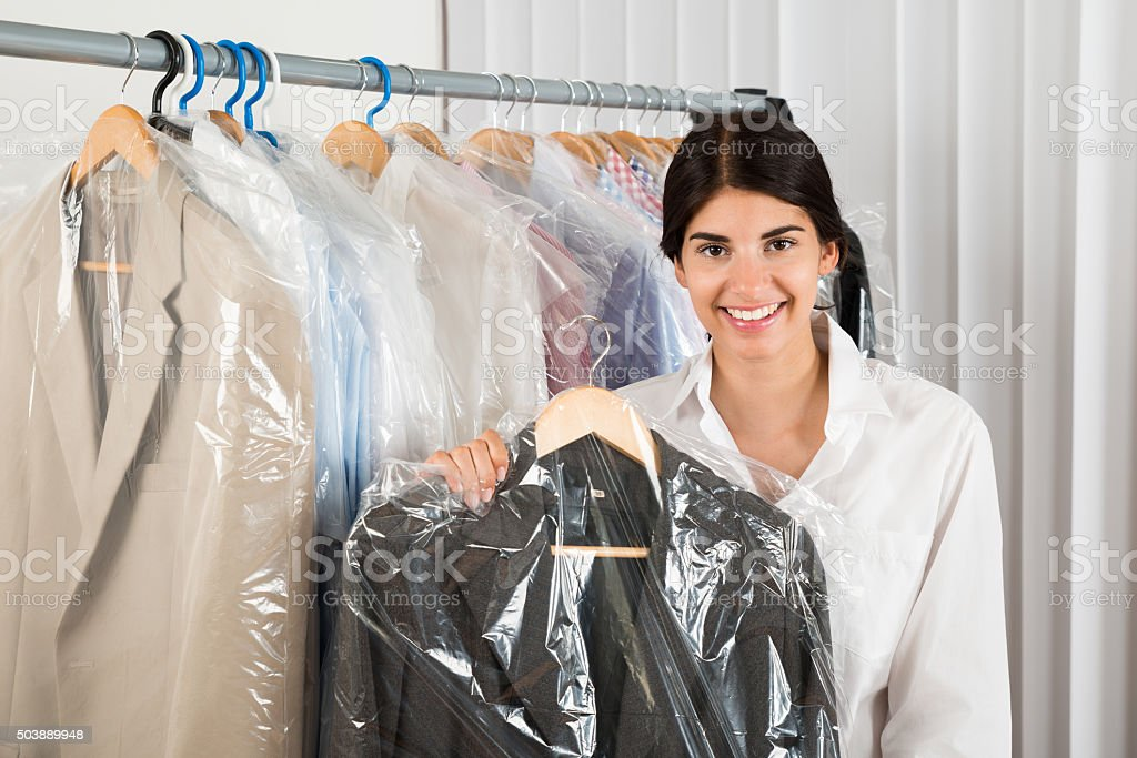 Woman Holding Suit In Shop stock photo