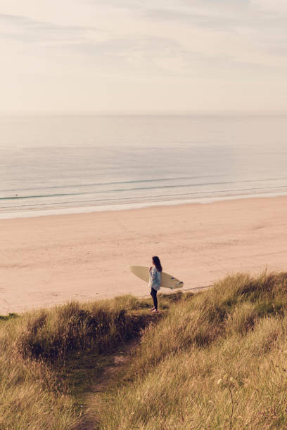 woman holding surfboard looking out over gwithian towan beach, cornwall, near sunset on a june day. - cornwall stock pictures, royalty-free photos & images