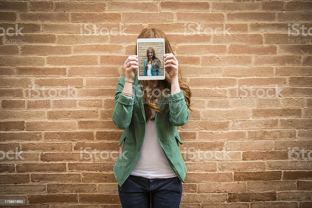 Woman holding tablet over her face with self photo stock photo
