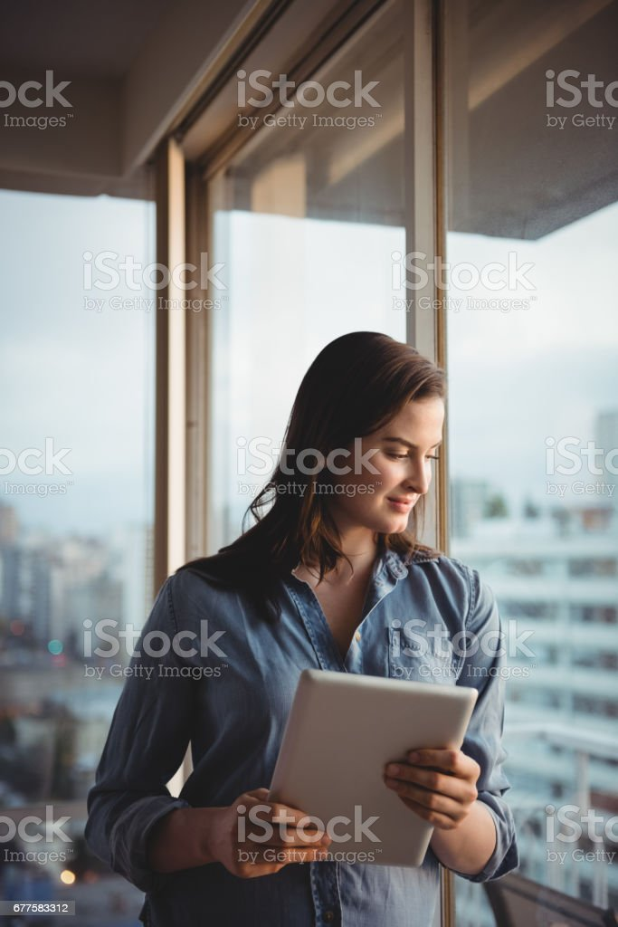 Woman holding tablet while looking through window royalty-free stock photo