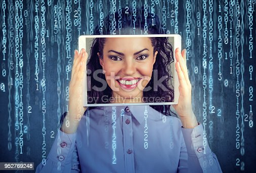istock woman holding tablet with her face displayed on a screen 952769248