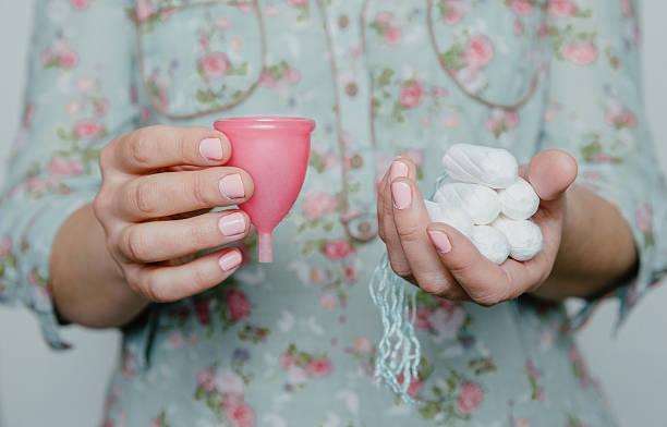 donna che tiene tamponi e mestruale tazza in mani - coppa mestruale foto e immagini stock