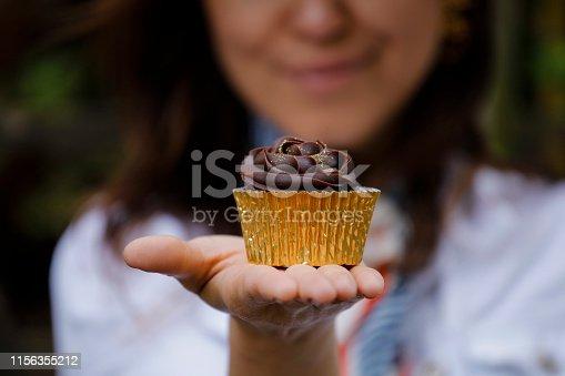 Woman holding tasty chocolate cupcake