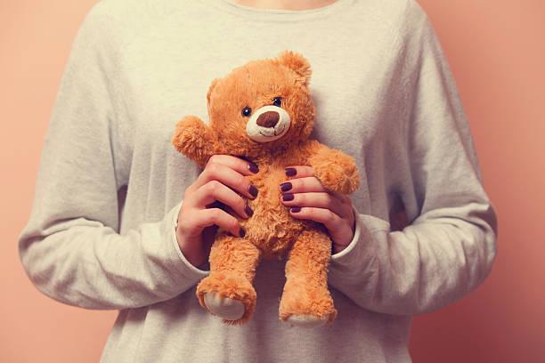 Woman holding teddy bear toy stock photo