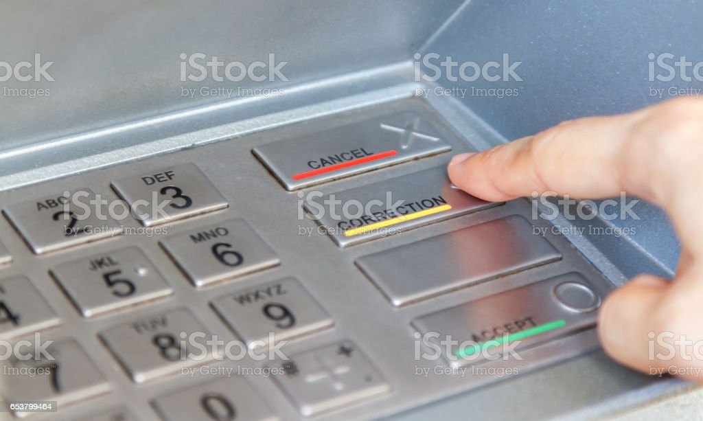 Woman holding the phone with mobile wallet and credit card on the screen against the background of the ATM,Closeup of woman hands using smart phone while typing on ATM, Slective focus. stock photo