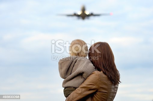 istock Woman holding toddler with airplane on background 493833268