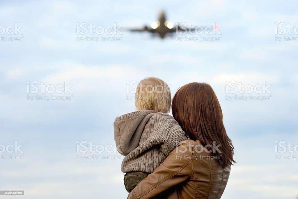 Woman holding toddler with airplane on background stock photo