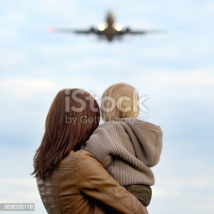 istock Woman holding toddler with airplane on background 508039176