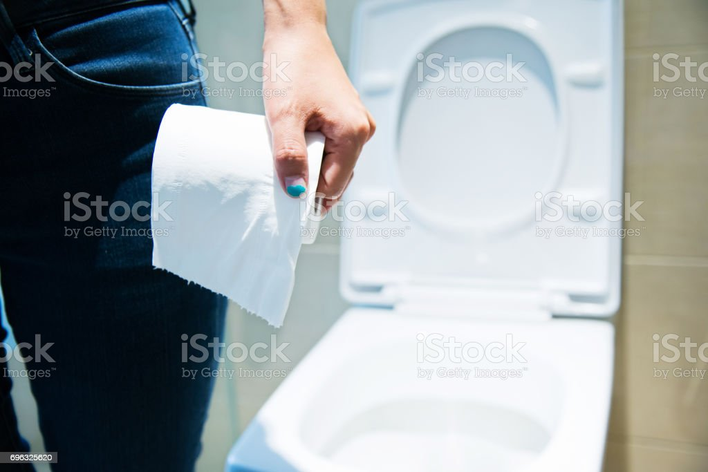 Woman holding toilet paper roll in bathroom stock photo