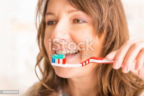 637874676istockphoto Woman holding toothbrush 469680803