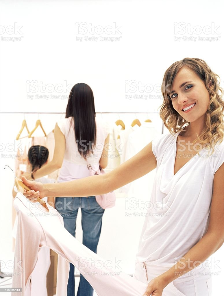 Woman holding top in clothes shop royalty-free stock photo