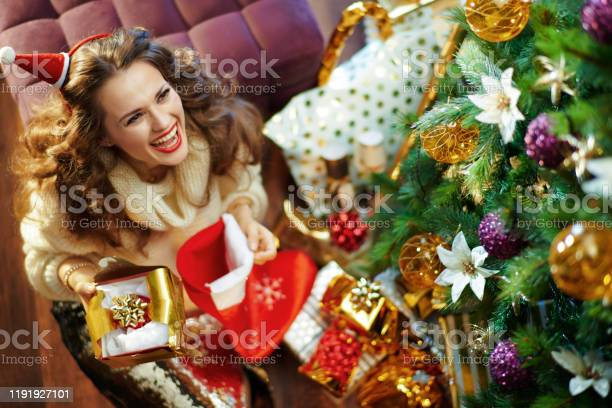 woman holding torn christmas gift which just got out of stocking