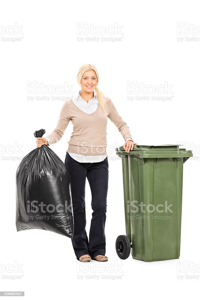 Woman holding trash bag next to a garbage bin stock photo