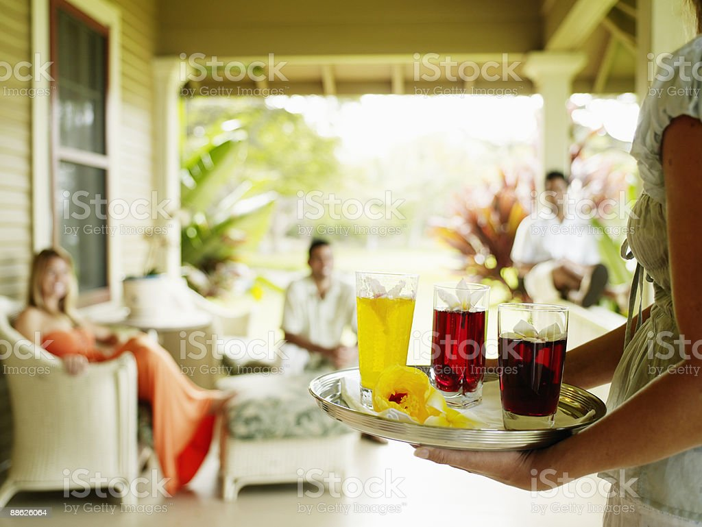Woman holding tray of drinks friends in background royalty-free stock photo