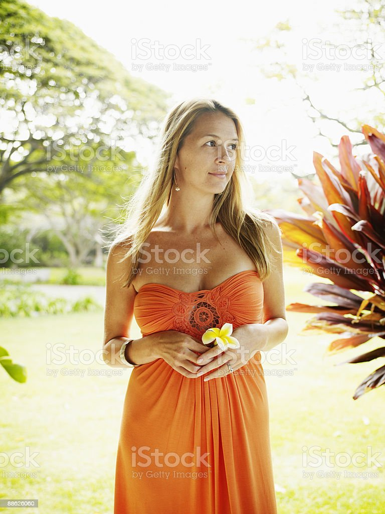 Woman holding tropical flower looking away royalty-free stock photo