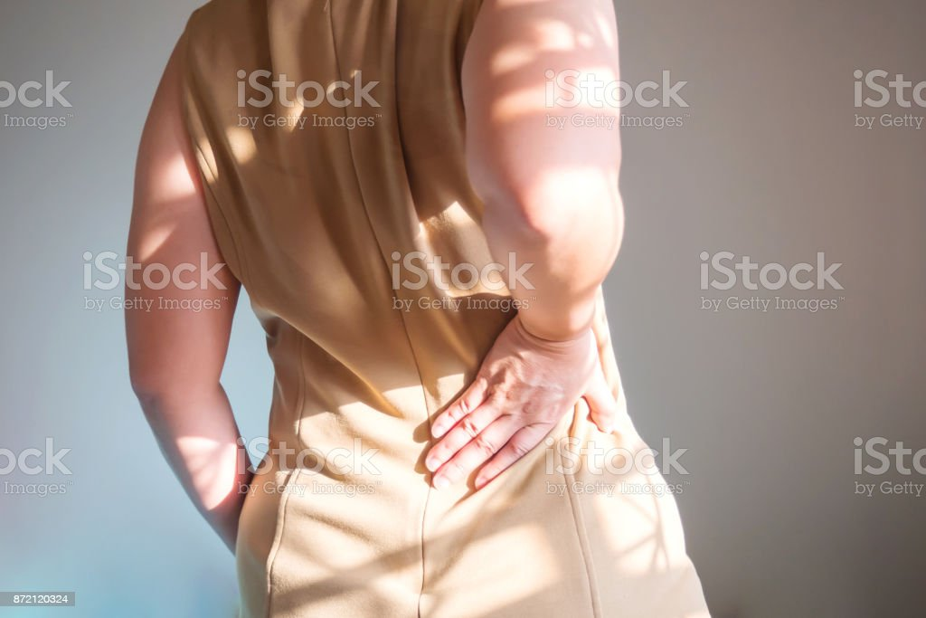 Woman holding two hands on back. Back pain at waist. Symptoms of Office Syndrome. Healthcare background. stock photo