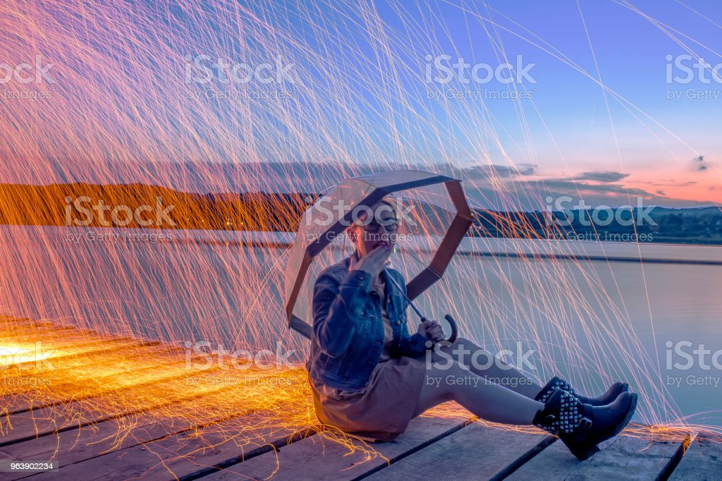 Woman holding umbrella against steel wool sparks - Royalty-free 30-34 Years Stock Photo