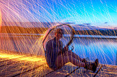 Woman holding umbrella against steel wool sparks