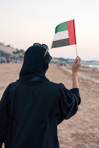 Woman holding United Arab Emirates flag on the beach