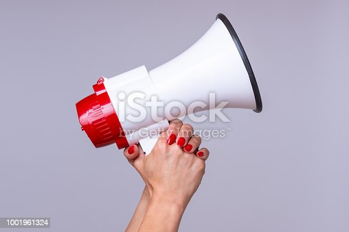 Woman holding up a loud hailer, bullhorn or megaphone as she prepares to stage a protest or demonstration to air her grievances