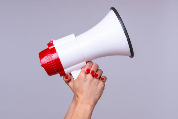 Woman holding up a loud hailer or megaphone Woman holding up a loud hailer, bullhorn or megaphone as she prepares to stage a protest or demonstration to air her grievances horned stock pictures, royalty-free photos & images
