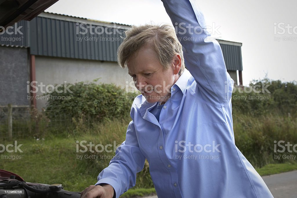 woman holding up hood of SUV royalty-free stock photo