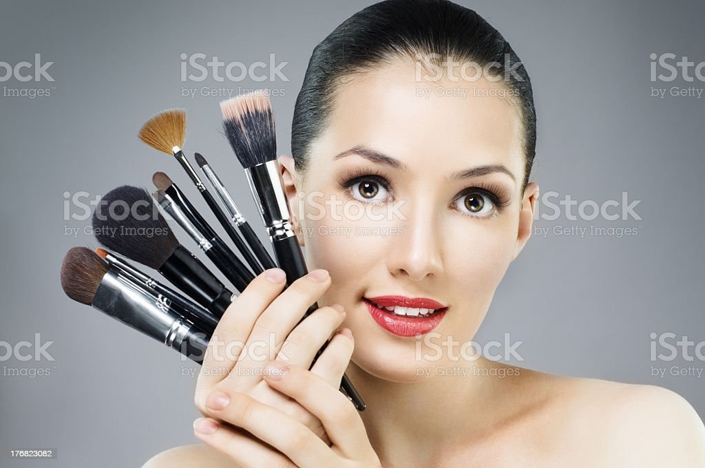 Woman holding up makeup brushes by her face royalty-free stock photo