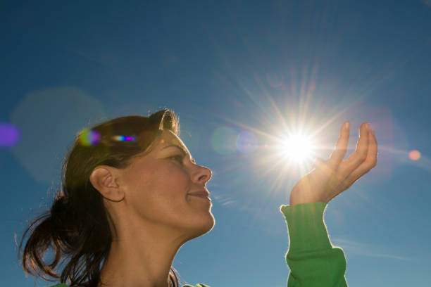 Woman Holding Up the Sun stock photo