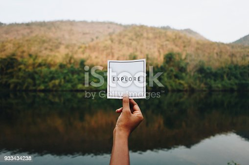 istock Woman holding up the word explore in nature 933434238