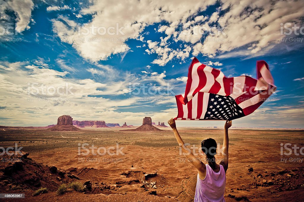 Woman Holding US Flag at Monument Valley stock photo