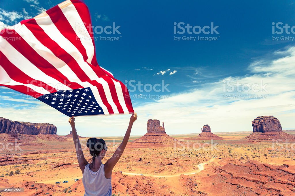 Woman Holding US Flag at Monument Valley, USA Landmark stock photo