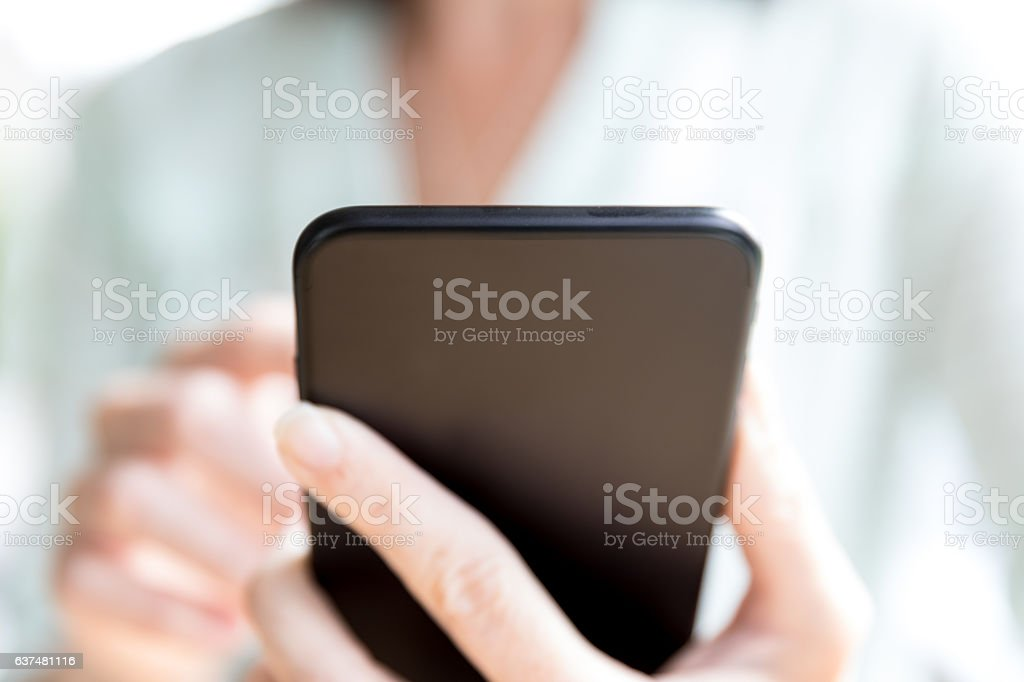 Woman Holding and Using Black Smart Phone in Coffee Shop