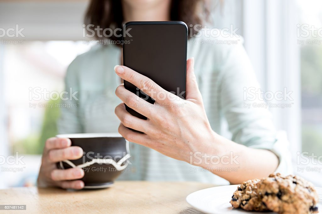 Woman Holding and Using Black Smart Phone in Coffee Shop while...