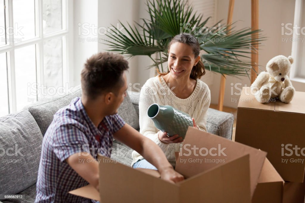 Woman Holding Vase Helping Man Packing Boxes On Moving Day Stock