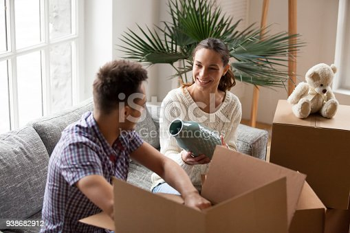 istock Woman holding vase helping man packing boxes on moving day 938682912