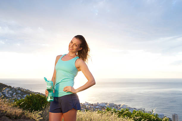 Woman holding water bottle by sunset by the sea stock photo