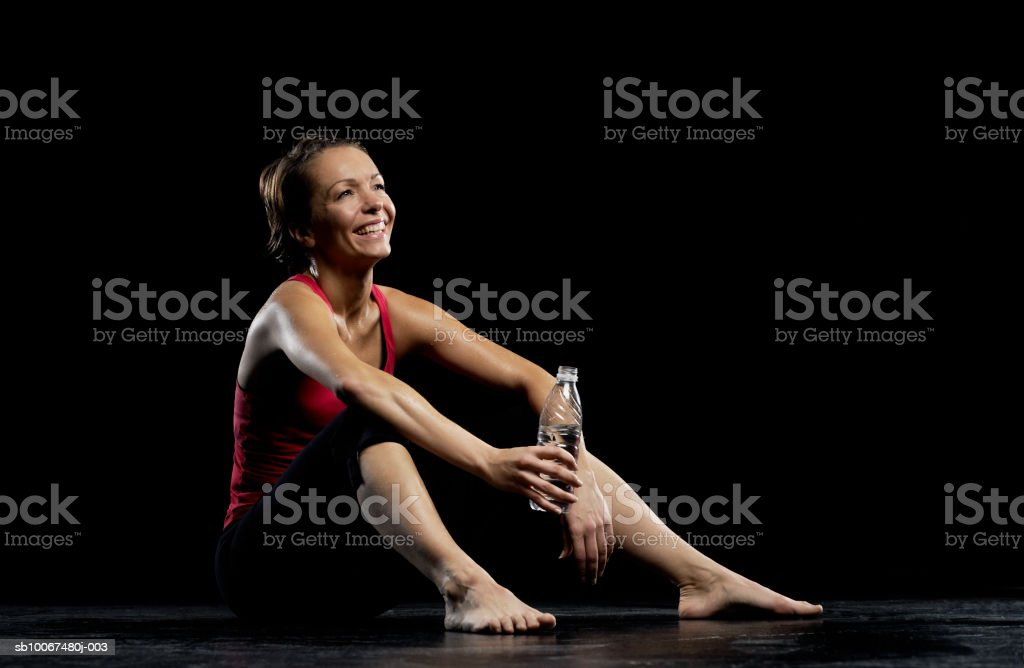 Woman holding water bottle, smiling royalty-free stock photo