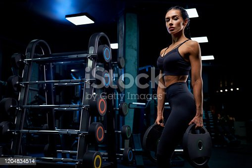 istock Woman holding weights near barbells. 1204834514