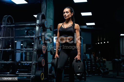 istock Woman holding weights near barbells. 1264091170